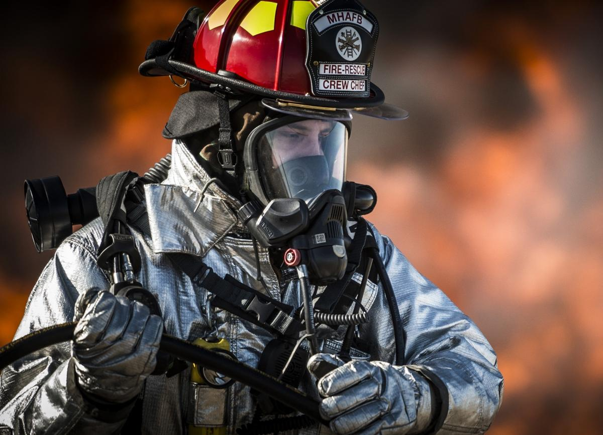 Firefighter in silver suit in front of flames